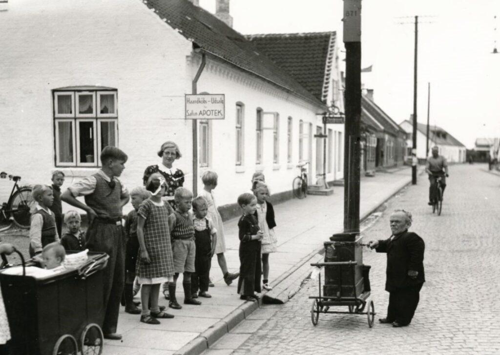 Musikalsk foredrag om lirekassen som social foranstaltning. Lirekassemand på gaden i Pandrup i 1936