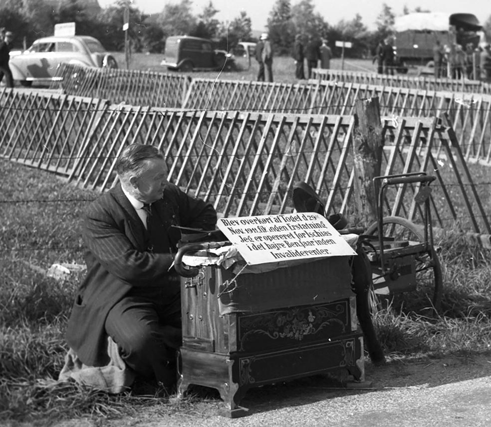 """Lirekassemændenes historie. Positivspiller på dyrskuet i Odense i 1938. Positivspillerne lagde ikke skjul på deres handicap og håbede på den måde måske at få lidt mere """"i hatten""""."""